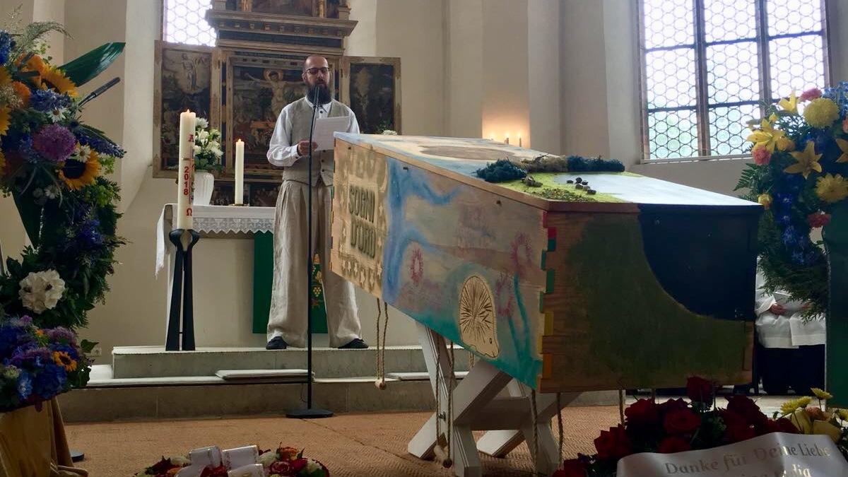 Ein Mann steht vor einem bunt bemalten Sarg vor einem Altar.