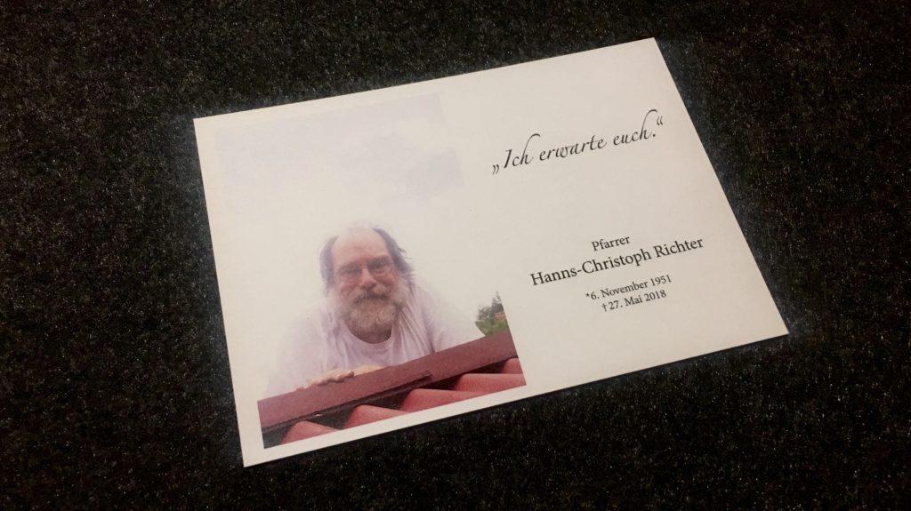 """Ein Mann mit Bart schaut aus den Wolken von einem Dach herab. Auf der rechten Seite steht """"Ich erwarte euch. Pfarrer Hanns-Christoph Richter. Geboren 06.November 1951. Gestorben 27. Mai 2018."""