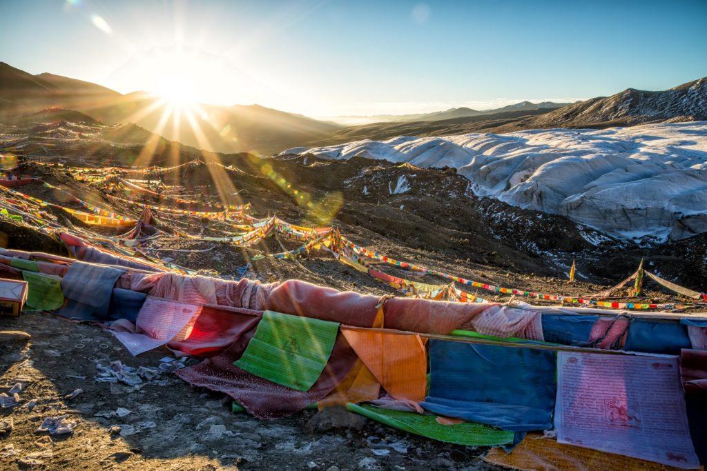 Das Foto von James Wheeler von Unsplash ziegt Leinen mit bunten Stofftüchern vor Bergen hinter denen die Sonne aufgeht.